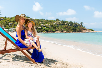 Beautiful mother lady in blue dress and beach straw hat with her pretty blonde cute daughter. Woman in a beach chair, little lady close her eyes. Happy family on the shore. Happy mothers day.