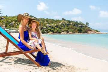 Beautiful mother lady with her pretty blonde cute daughter in dress and beach straw hat. Woman in a beach chair and little girl smile to the camera. Happy family on the shore. Happy mothers day.