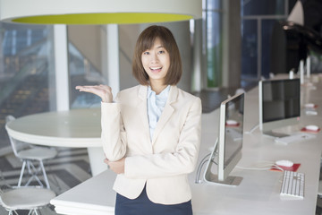 Attractive asian business woman showing something on workplace