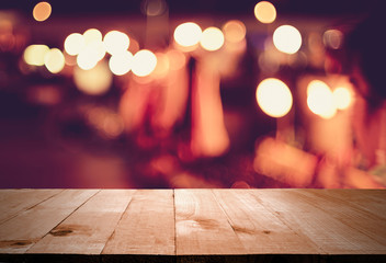 wooden table in front of abstract blurred lights in bar