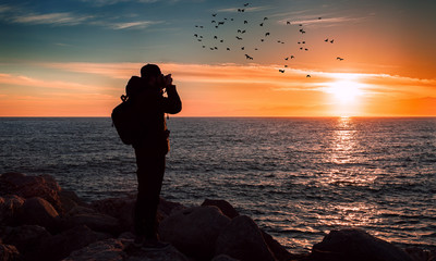Young Man Photographer is Taking a Picture of a Beautiful Sunset over the Sea. Flock of Birds on the Sky