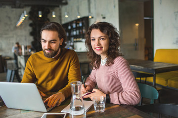 Young hipster male and female working laptop together in cafe