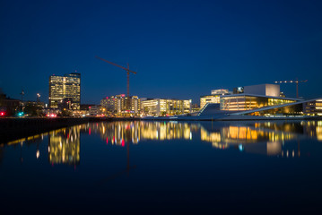 Lights from Oslo Opera House and Oslo center reflected in the water.