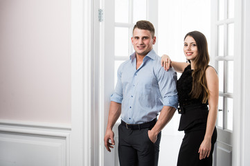 Couple of  young stylish people in the doorway home interior loft office