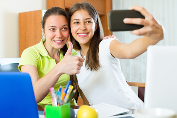 Girls doing selfie with smartphone at home.