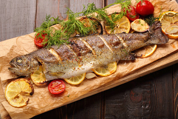 Baked fish with lemon on wooden background