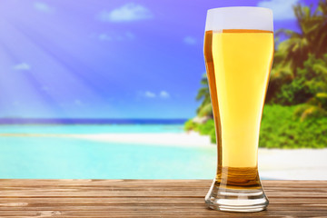 Glass of cold fresh beer on table, on sea or ocean background