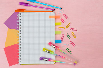 Office set with notebook, colored pens and clips on pink background