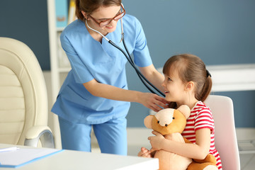 Doctor examining girl with stethoscope in the office