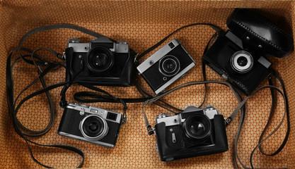 Old cameras inside vintage suitcase.