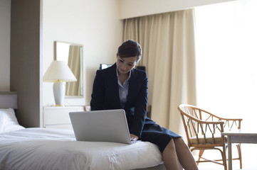 Women are working in the personal computer in the hotel's business trip destination