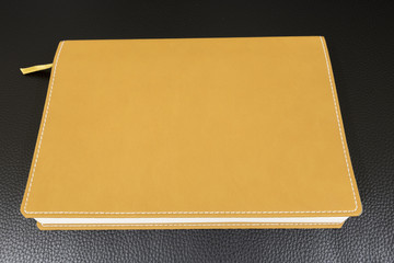Book Yellow Leather on a Black Leather