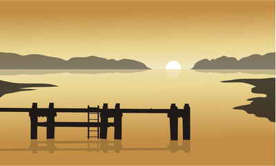At sunrise in sea with pier silhouette