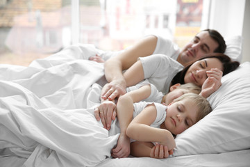 Family sleeping in bed, closeup