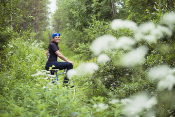 Portrait of mid-adult woman on bicycle in forest