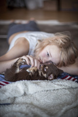 Teenage girl lying on floor and playing with puppy