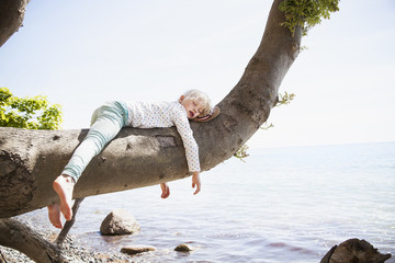 Young girl sleeping on branch by sea