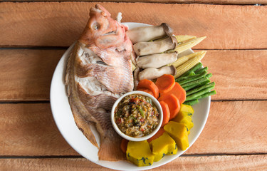 Steamed Nile tilapia  fish and vegetables, served with sauce on
