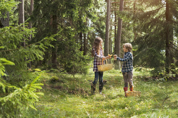 Brother and sister picking mushrooms in forest