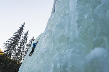 Man climbing up on frozen waterfall