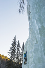 Man climbing up on frozen waterfall