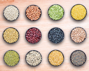 Mixed beans and lentils in bowl on wooden background.