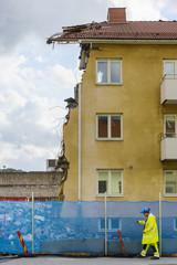 Man walking by demolished house
