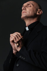 Priest standing with eyes closed and praying