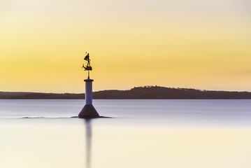 Coast with statue at sunset