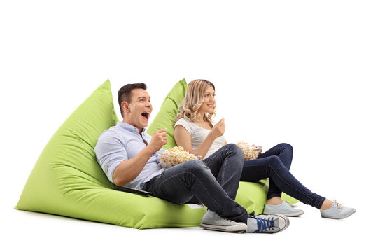 Couple eating popcorn seated on beanbags