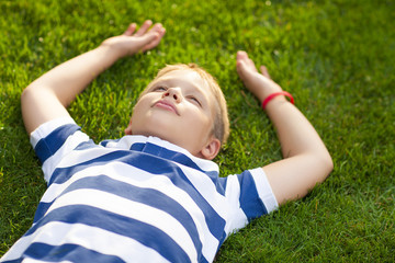 Little boy lay down on the grass