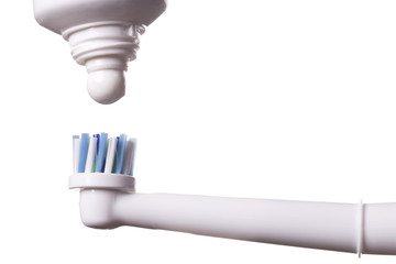 Close up of electric toothbrush with blue bristles and tube with paste bubbled at its opening on white background