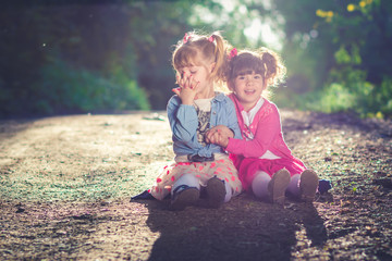 Cute twin sisters sitting on dusty road. Hugging and kissing each other.