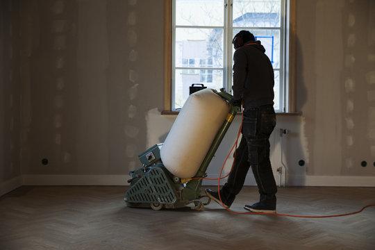 Man cleaning wooden floor with floor scrubber