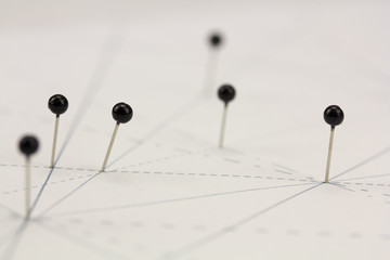 Black pins in paper linked by lines