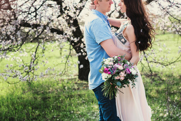 Young couple in love outdoor.Stunning sensual outdoor portrait of young stylish fashion couple posing in spring near blossom tree