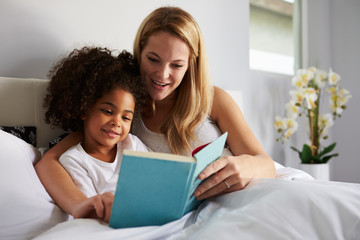 Caucasian mum and black daughter read a book together in bed