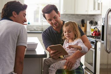 Male gay couple using tablet with their daughter in kitchen