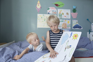 Two little brothers on bed at children's room watching picture book