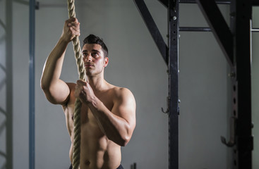 Young man exercising and preparing to climb the rope