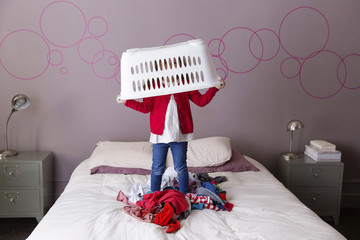 Little girl playing on parents' bed with laundry basket