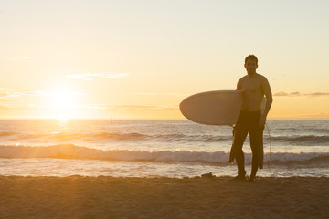 Surfer standing on the beach at sunrise