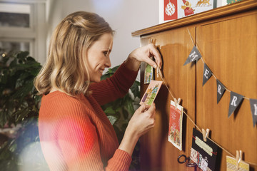 Woman hanging up Holiday cards for decoration
