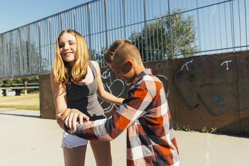 Teenage boy teaching his girlfriend skateboarding