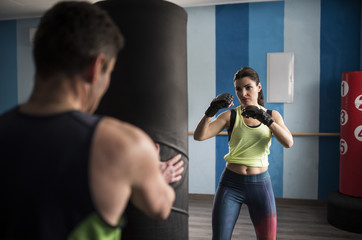 Mature woman training boxing and kickboxing in gym