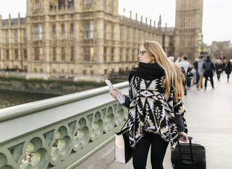 UK, London, young woman walking along Westminster Bridge with her luggage