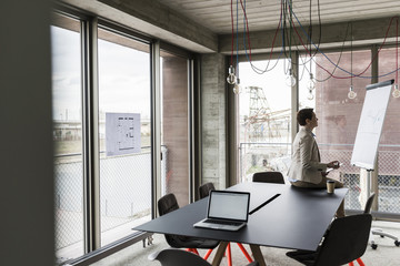 Businesswoman looking at flipchart in conference room