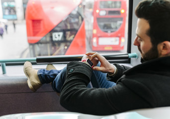 UK, London, young man in a double-decker bus using his smartwatch