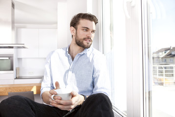 Young man with coffee cup sitting on window sill looking through window