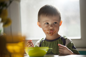 Serious looking little boy eating chocolate